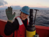 Image of Becki Beadling holding a large sensor with a blue hardhat on standing on a large red boat in the arctic ocean